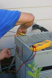 technician working on outside unit of air conditioner