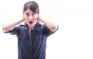 woman covering her ears with shocked expression on face